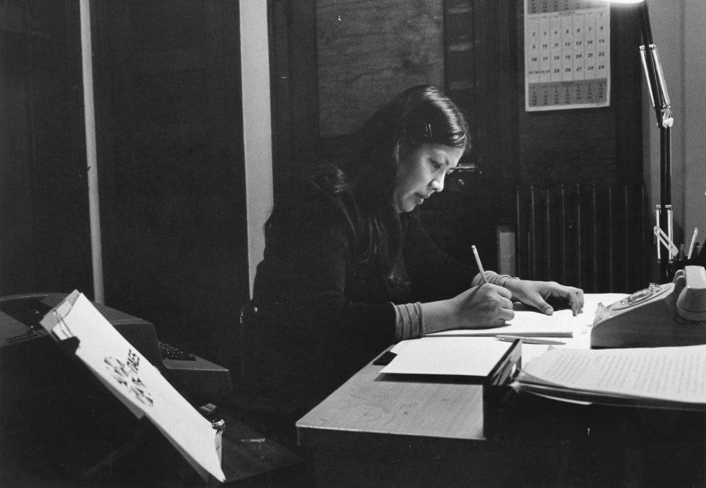 A picure of NAES graduate Georgiana King Keahna working at a desk at NAES. She headed the only workforce employment and training program for American Indians in Chicago.